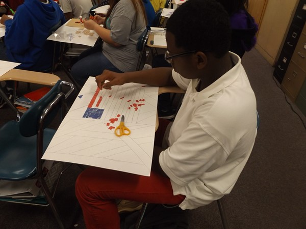 TK student producing art with colored paper squares.